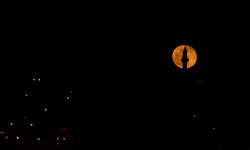 Full moon behind a Turkish mosque minaret
