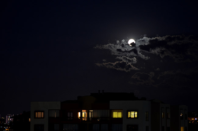 Full moon and clouds over apartment