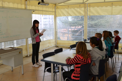 A junior high student tells the elementary students about the water crisis.