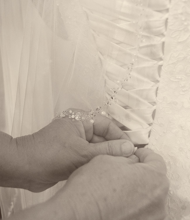 Lacing the back of her dress